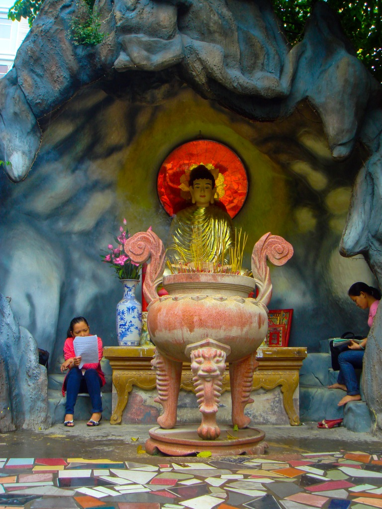 Two young women study next to a Buddhist statue