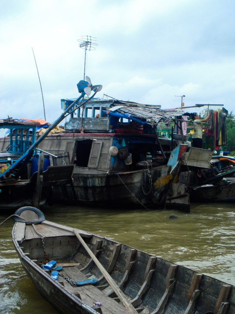 Different vessels crowd together in a small floating village