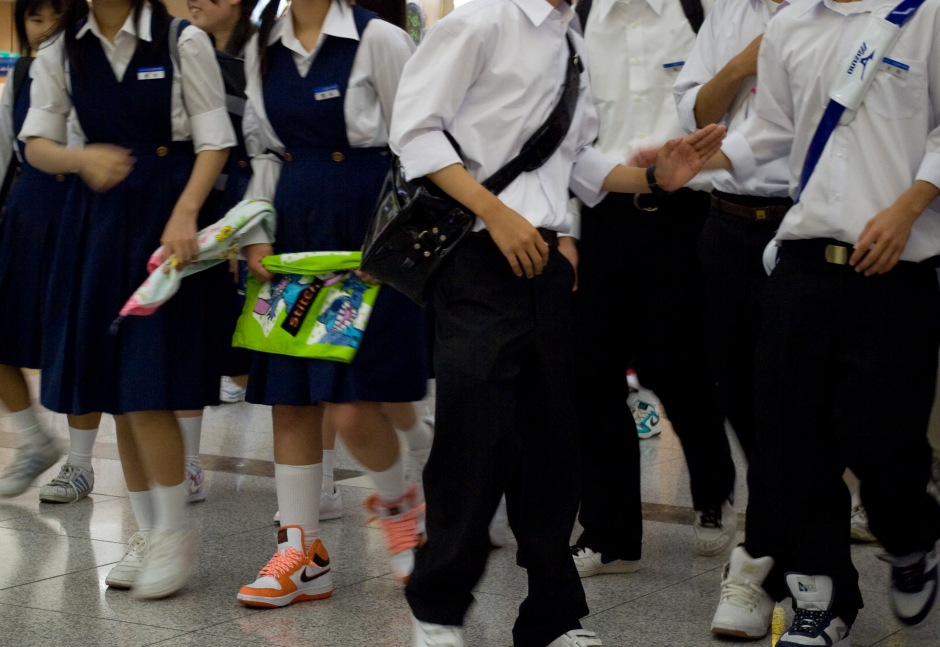 A group of school children migrate through a subway station in Osaka