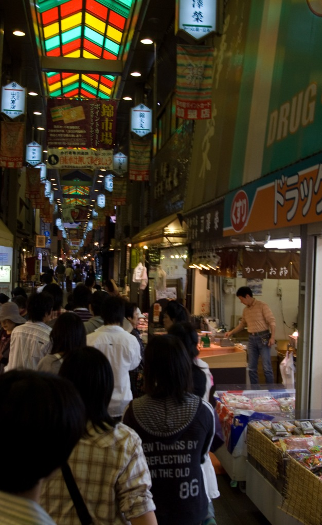 Shoppers crowd the dark alleys of a popular market in Kyoto