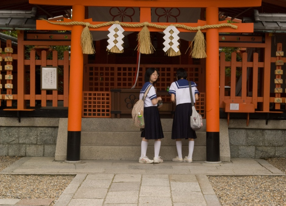 Young girls offer prayers and bows at a Torii Gate in a Shinto shrine