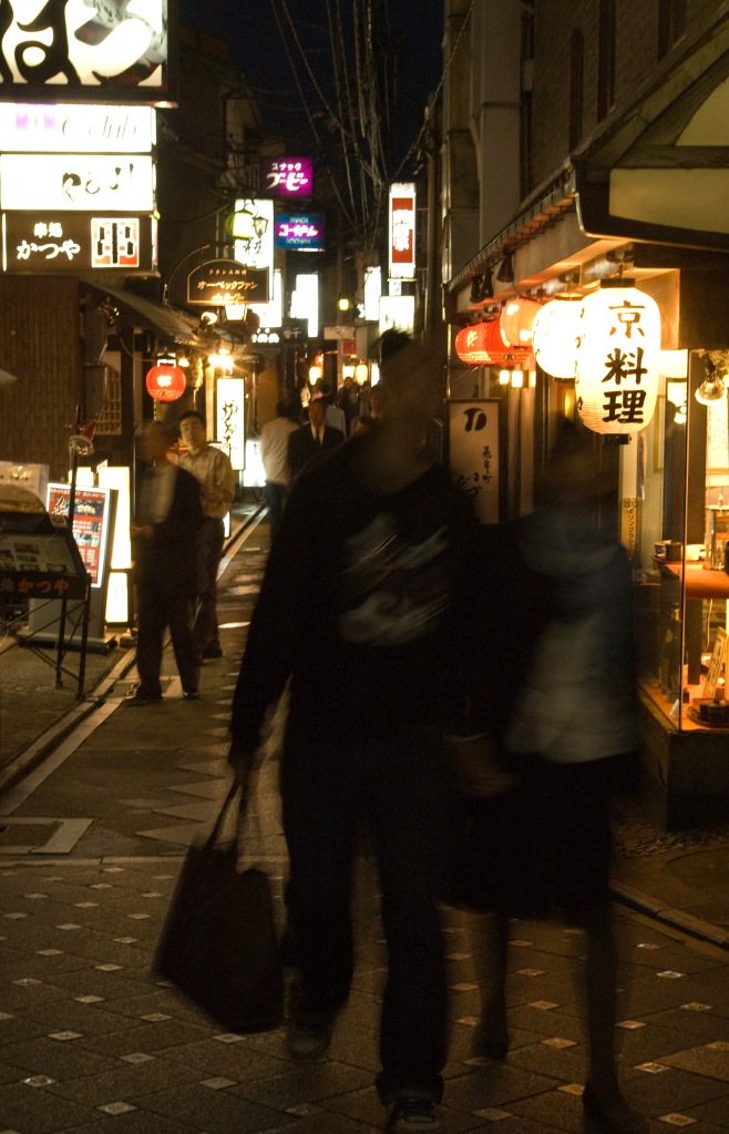 A young couple comes out of a popular street at night