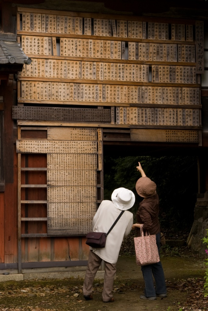An elderly couple review prayer boards at a Shinto Shrine