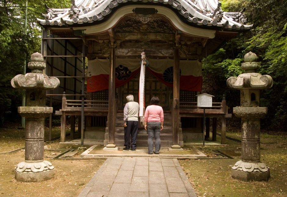 An elderly couple offer prayers and bow at a Shinto shrine