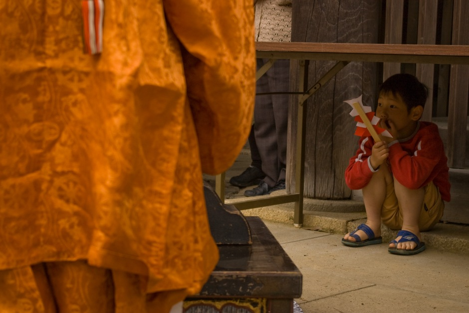 A young boy clutches a prayer stick and looks on to a Shinto spring ceremony