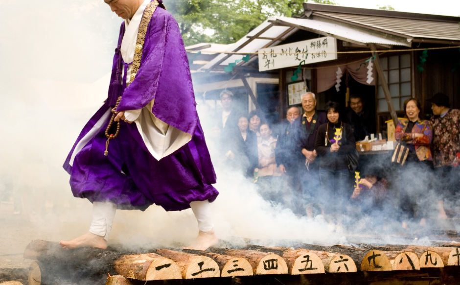 A Shinto priest walks over burning logs during a spring ceremony