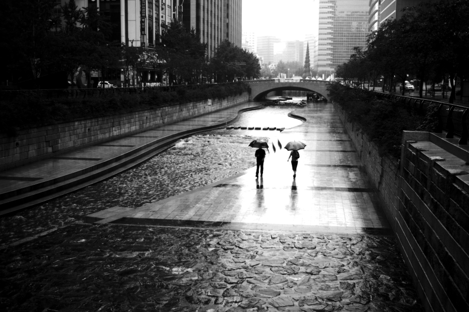 People stroll along the Cheonggyecheon, despite the rain