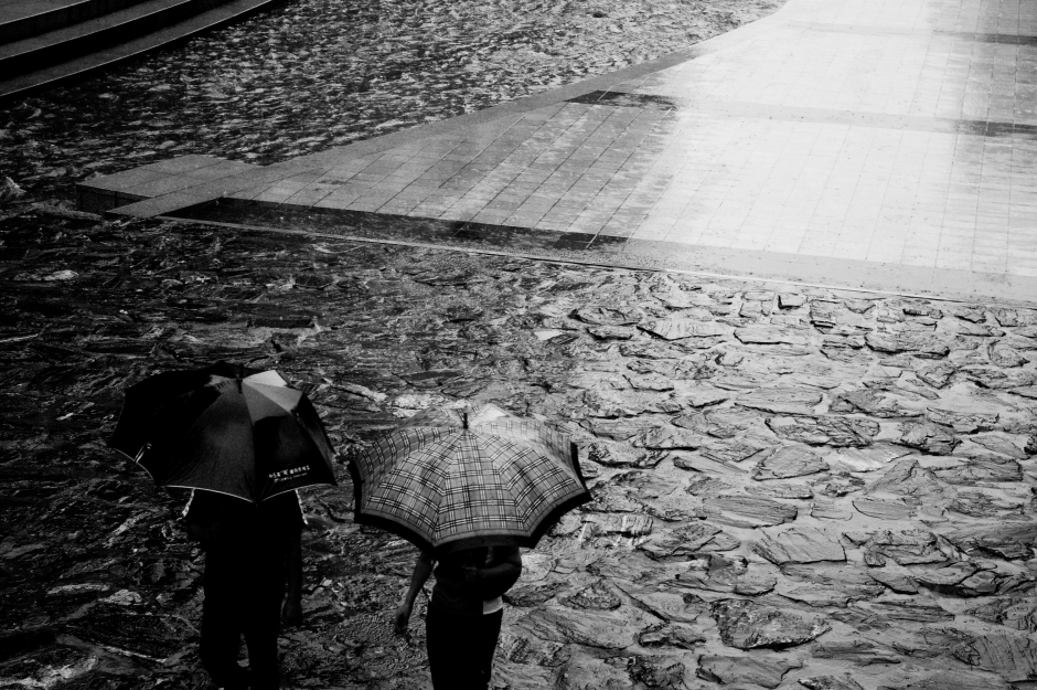 Umbrella laden people stroll during a rainy holiday in Seoul