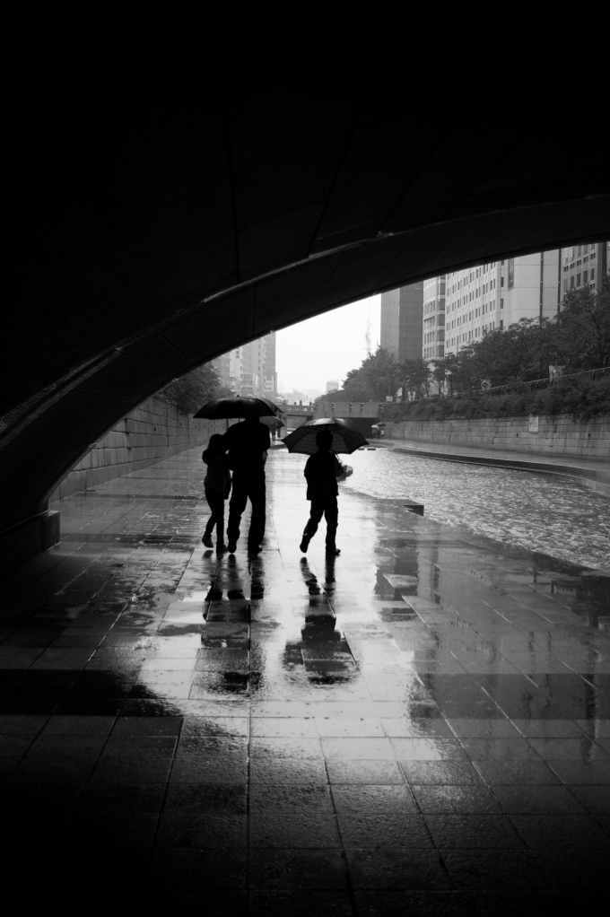 A family strolls along a rainy stream
