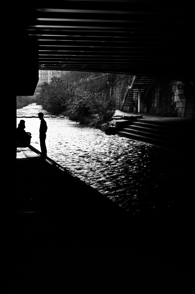 An elderly couple relaxes under a bridge on a rainy holiday