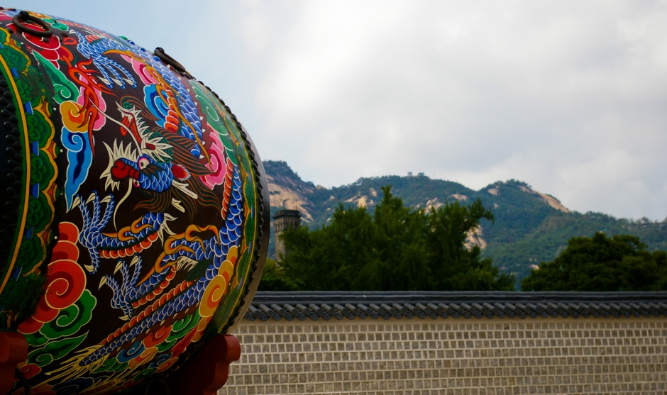 A traditional painted drum faces a nearby mountain range, Gyeongbokgung, Seoul