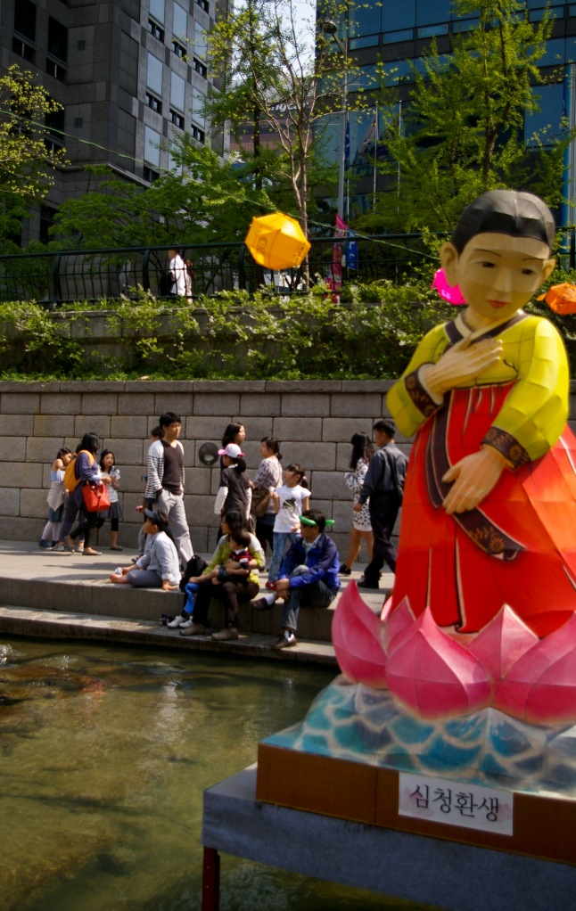 A lantern of a woman wearing traditional Korean clothing floats in the Cheonggyecheon, Seoul