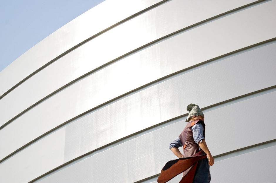 A man in historical Korean clothing stands next to the old City Hall building