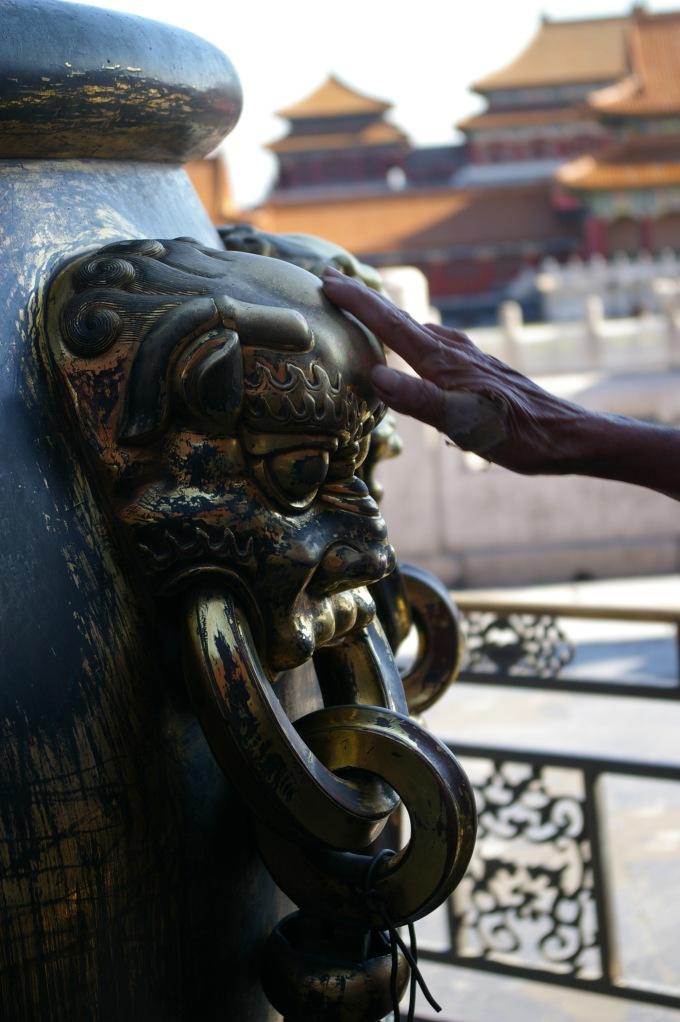 An elderly person rubs a dragon head for luck