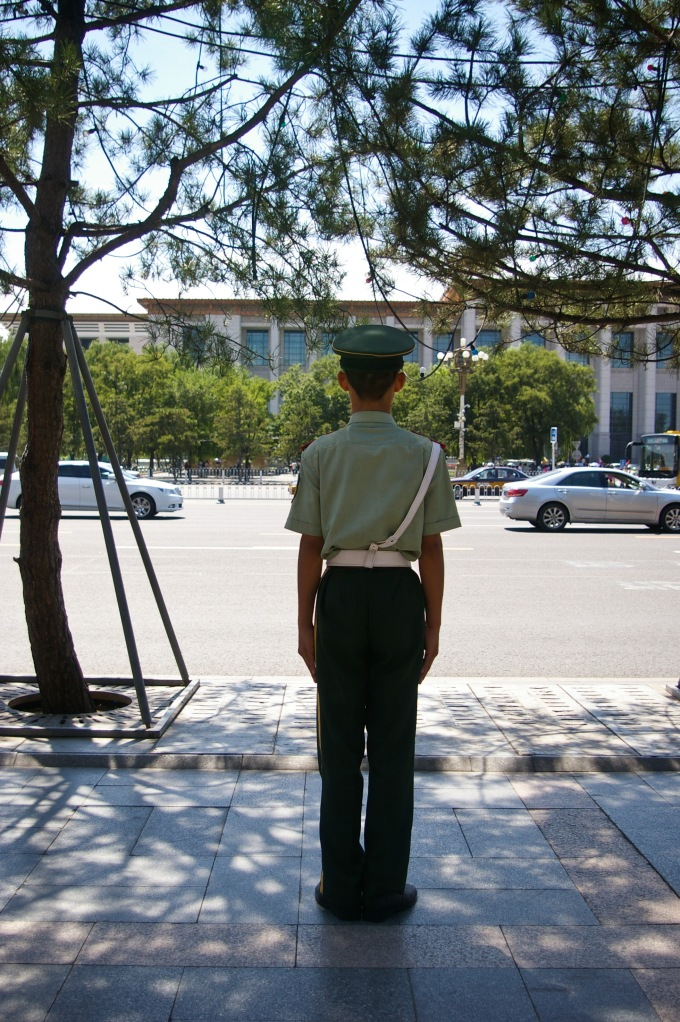 A young police officer stands at his post