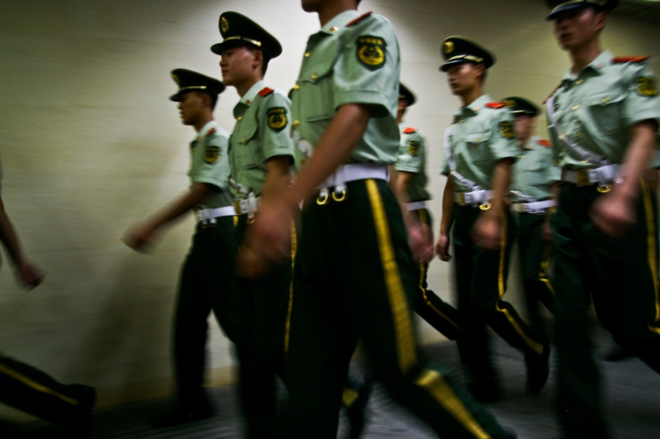 Young police officers march through a subway station in China