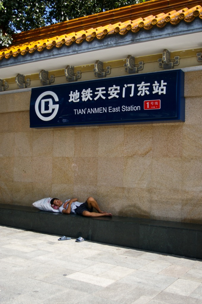 A man rests in the shade of the Tian'anmen Station