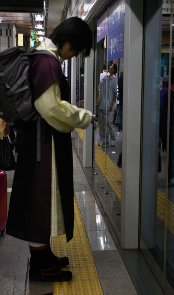 A young man in traditional Korean clothing waits for the subway