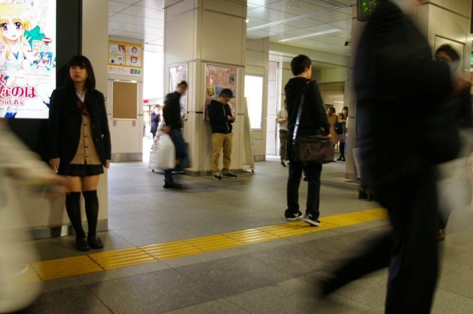 A young girl waiting amid the hustle of Akihabara Station