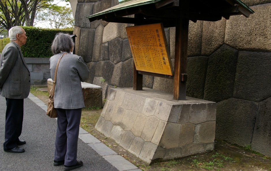 An elderly couple reads a plaque as they enter the Kokyo Gaien National Garden
