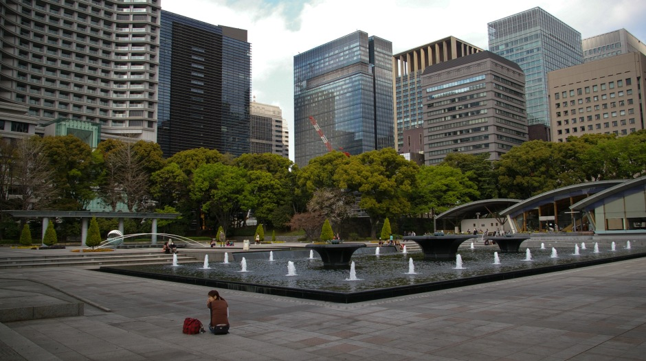 A woman sits alone in the Kokyo Gaien National Garden