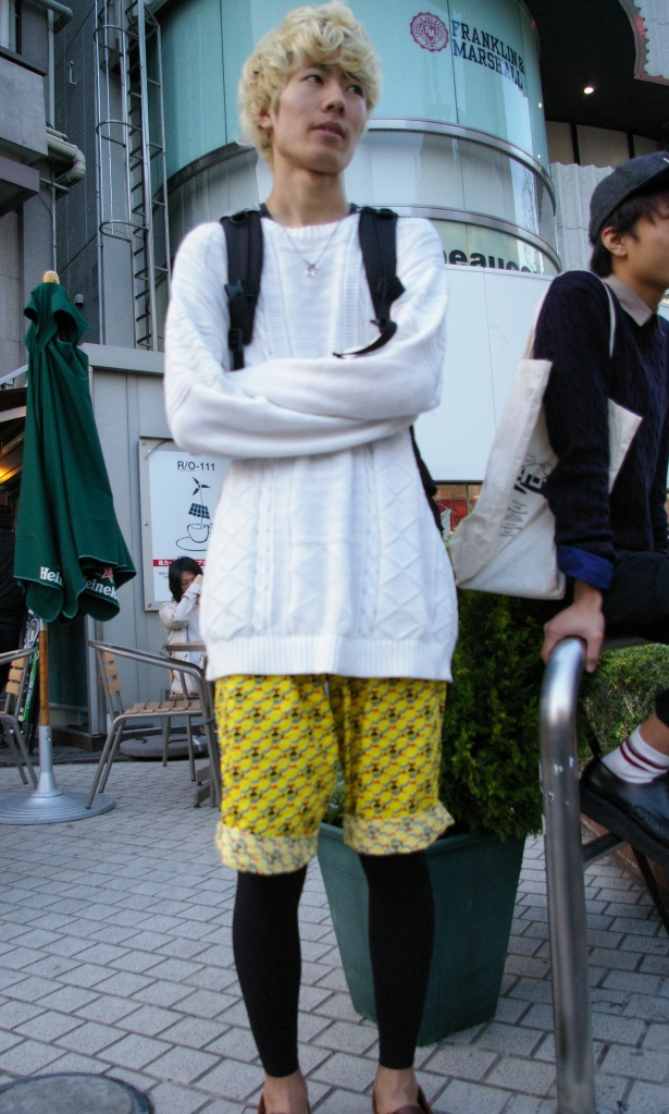 A young man waits for admirers on a corner in Harajuku