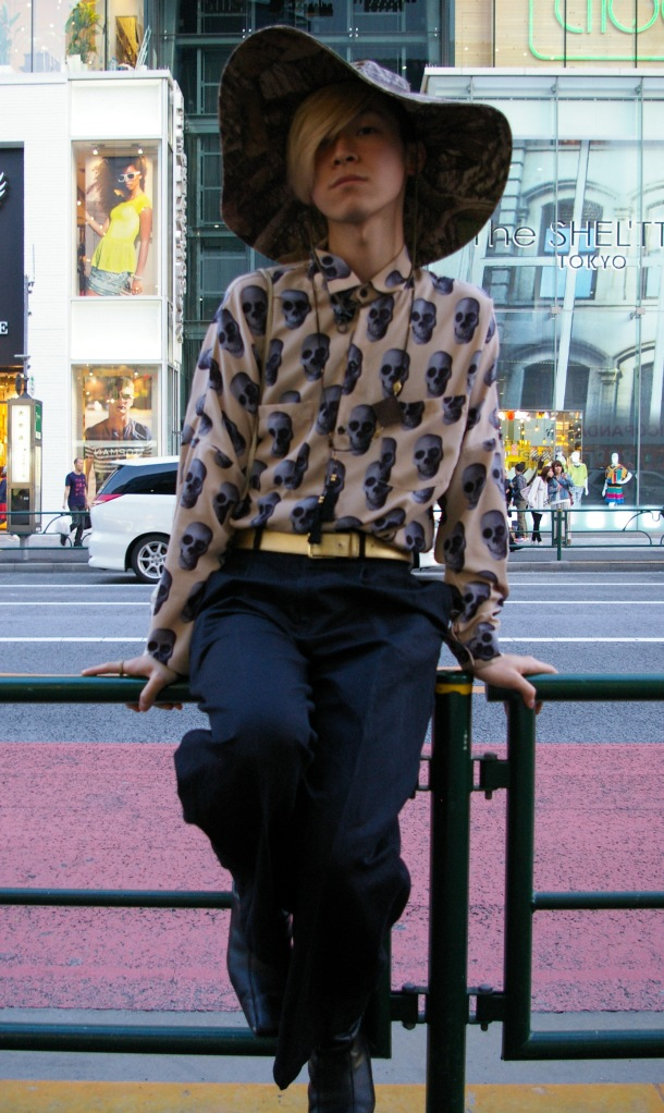 A young man poses for passersby in Harajuku