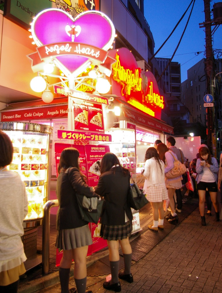 Young shoppers wait in line for waffles under the neon lights