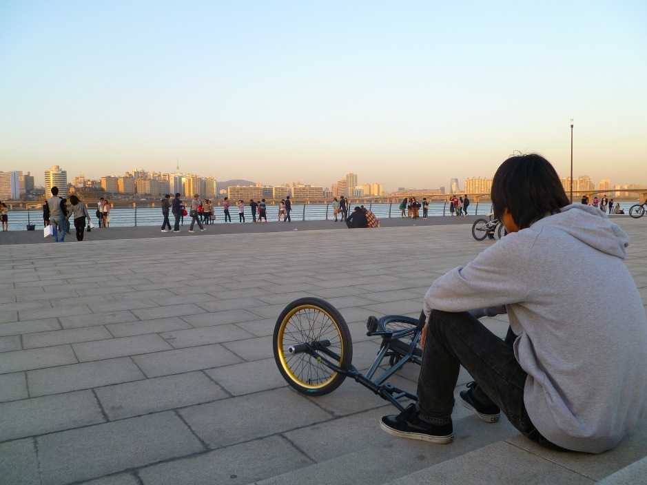 A trick cyclist relaxes at twilight on the Han River, Seoul